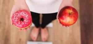 Ragazza su bilancia mentre sceglie se mangiare una mela o un dolcetto