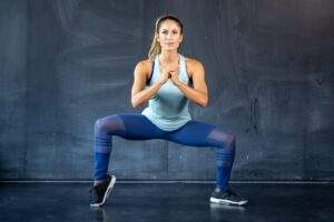 Ragazza che alterna squat con plie squat